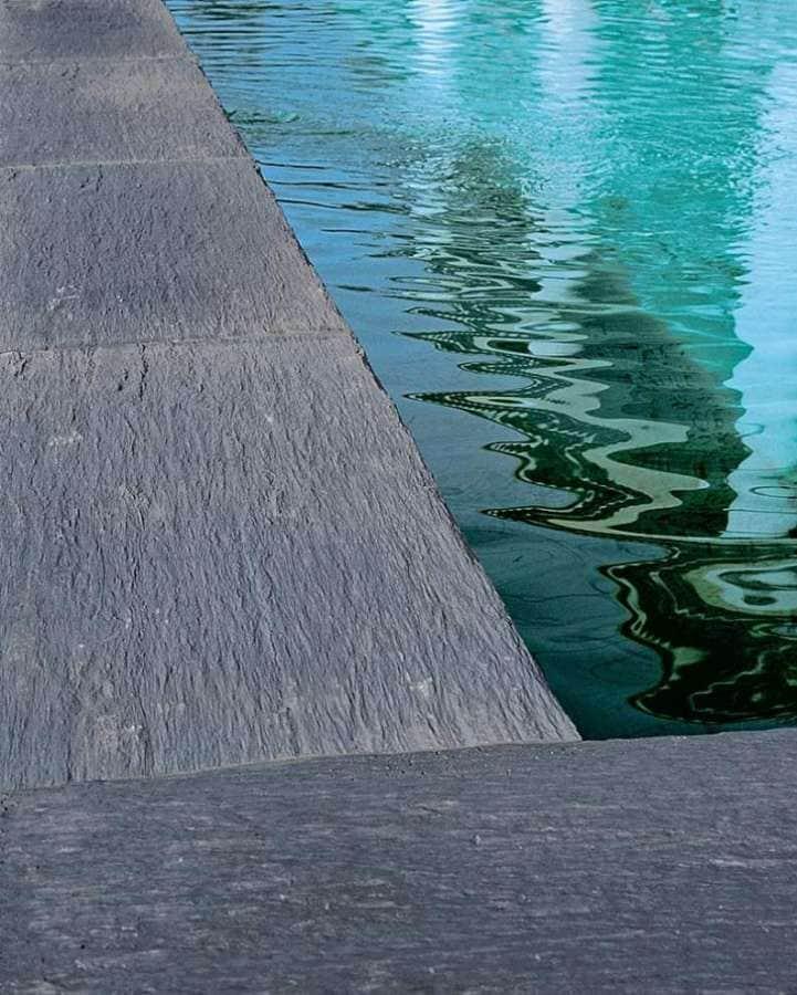 Les dalles en pierre reconstituée Ardoisière s'inspirent directement des ardoises de la carrière de Travassac, en Corrèze, particulièrement prisées par les Architectes Bâtiments de France. Elles évoquent ainsi l'aspect du schiste, avec un travail décoratif remarqué sur la surface. Ardoisière vise tous les styles et lieux. En margelle de piscine, elle offre des dimensions de 60x27 cm, avec toujours en ligne de mire les propriétés ingélives et anti-dérapantes. ©Pierra