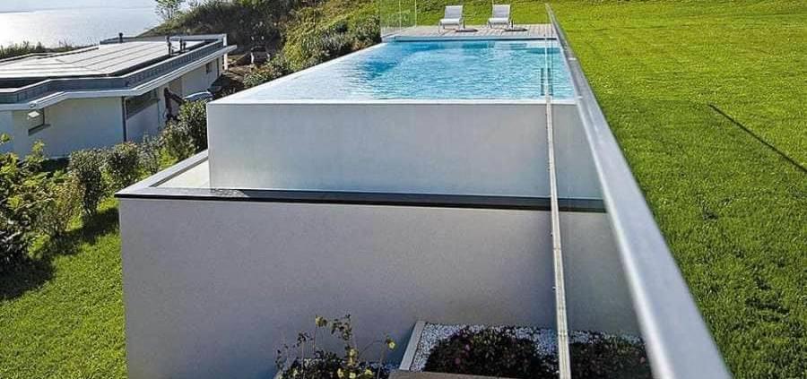 Véritable prouesse technique, cette piscine à débordement est une vraie création esthétique. Avec des dimensions de 10,85 x 4,85 mètres, elle joue avec le terrain et la vue. Le débordement, ici, prend tout son sens, pour ne faire qu'un avec l'horizon, souligné par le lac. On retrouve une harmonie avec la maison, par le biais du garde-corps en verre, tandis que la plage en bois, vient rompre avec l'esthétisme global. Réalisation Nicollier Piscines (Fully). Photographe M.Delairon. ©Carré Bleu distribué par Teréo Piscines (Charbonnières)
