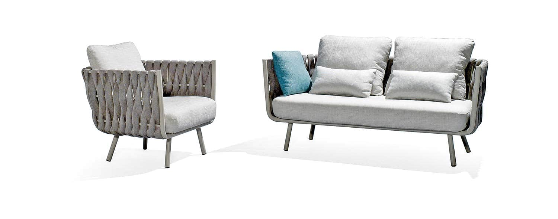 Salon de jardin présentant un sofa et un fauteuil club, avec structure en aluminium laqué par poudrage, revêtue d'un tressage vertical en caoutchouc cellulaire. Design Monica Armani. ©Tribù