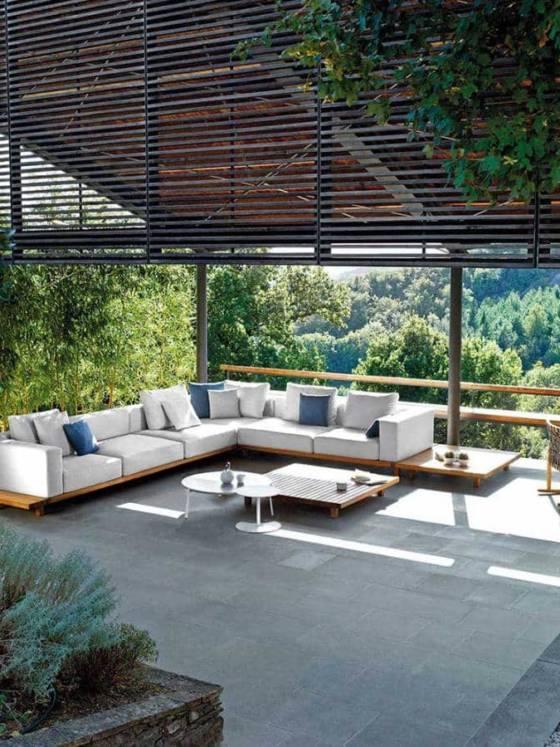 Collection modulaire comprenant un ensemble sofa, sièges et tables de jardin. Sofa à trois places, près du sol, avec assises et dossiers capitonnés piètement en bois. Design Piergiorgio Cazzaniga. ©Tribù
