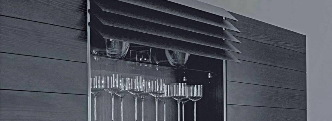 Cet élément mural se distingue par une façade en lamelles de verre de 13 cm. Il vous suffit d'effleurer le bas de l'élément afin que les lames glissent, via un système motorisé. Le design surprend et insuffle au sein de l'espace cuisine une note supplémentaire d'élégance et également de fonctionnalité. ©Häcker
