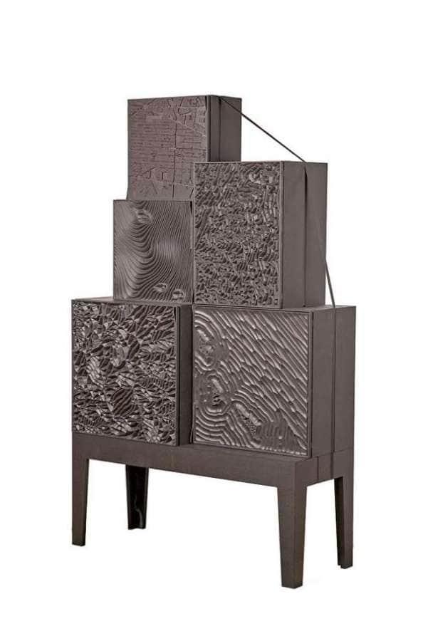 Ce système de coffres se présente comme des modules de monolithes noirs, avec une surface sculptée dans la masse. Une perspective bluffante disséminée sur 5 blocs de bas reliefs d'ébène. ©Ibride