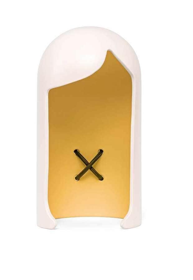Lampe de table, inspirée d'une coiffure classique, qui crée une lumière douce par un jeu de réflexion, avec un détail subtil, le smiley en croix, à l'intérieur. LED et céramique. ©Soon Saloon