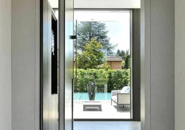 Cette porte d'entrée pivotante sur-mesure, 1,40 x 2,60 mètres, trouve sa pertinence dans l'axe architectural. En alu laqué, côté extérieur avec habillage en bois côté intérieur, elle enchâsse un isolant entre les deux faces. Le pivot se pare d'un frein, pour un mouvement contrôlé à l'ouverture et à la fermeture. Réalisation Laurent Guillaud-Lozanne, architecte D.P.L.G. Photographe Frenchie Cristogatin.