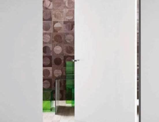 La brillance de la laque blanche apporte une profondeur supplémentaire. La porte pivotante Compass permet de mettre en communication des pièces avec légèreté, tout en étant rapide, silencieuse et invisible une fois refermée. ©Lualdi