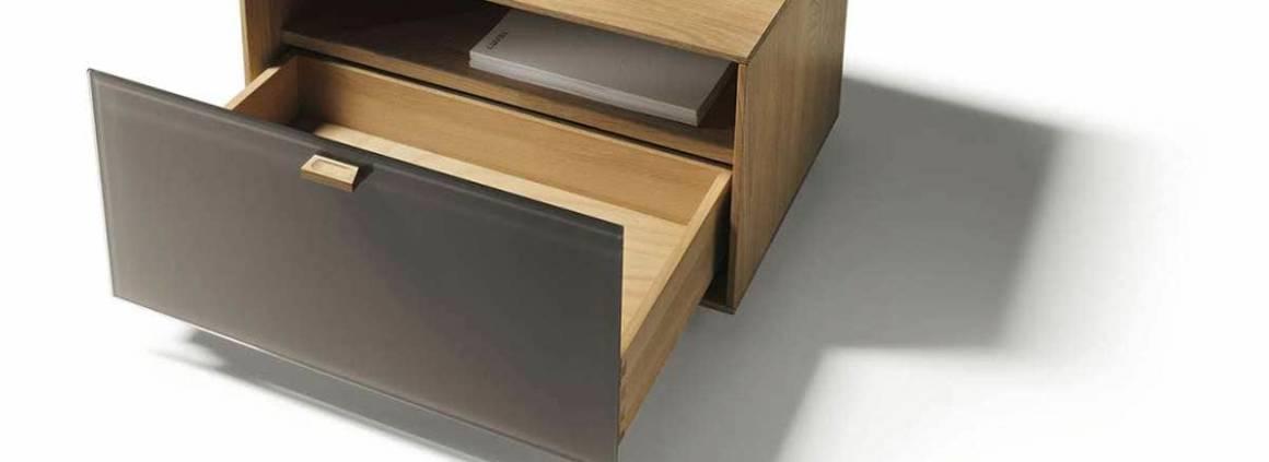 Meuble de chevet déclinable en 8 variations de bois. Façade en verre laqué coloré, brillantes ou mates. ©Team 7