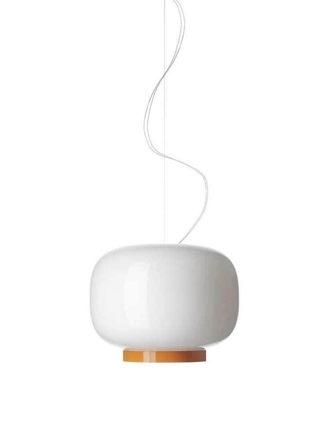 Le nom de cette suspension est japonais, pour désigné des lanternes traditionnelles en papier. Aux côtés de la 1ère version, cette nouvelle donne la parole à un diffuseur blanc et un «socle» coloré. En verre soufflé peint. Design Ionna Vautrin . ©Foscarini