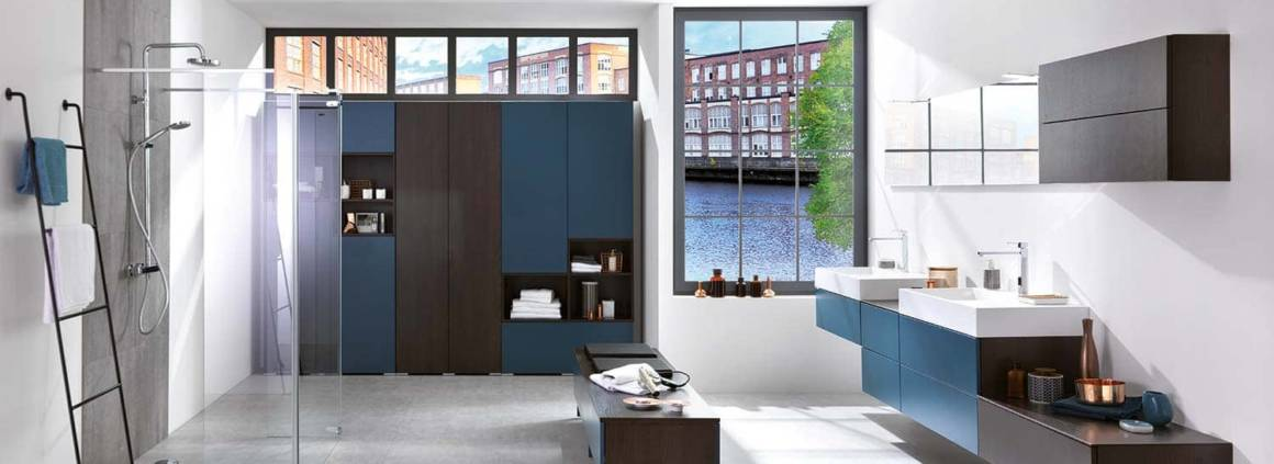 Une salle de bains qui joue avec les contrastes du bois sombre Maverick et le Moody Blue, toucher velours. Ils composent le mur armoire, prompte à accueillir tous vos accessoires, équipé de rangement Domino L, modulables. ©Schmidt