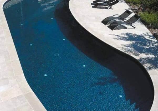 Cette rénovation s'exprime par une redéfinition de cette piscine de forme livre réalisée en béton armé hydrofuge, avec un escalier maçonné droit de 4 marches. Le bassin de 10 x 2,80 x 4,10 mètres révèle une profondeur moyenne de 1,65 mètre en pente régulière. Aujourd'hui, le revêtement intérieur est en carrelage, les margelles et les plages en pierre naturelle (calcaire d'Egypte). La piscine se dote d'une filtration à sable, d'une pompe de filtration à vitesse variable, un traitement de l'eau au brome avec régulation automatique, d'une pompe à chaleur, projecteurs LEDs. Réalisation Carré Bleu Nicollier Piscines & Paysages. Photo Sébastien Keckeis. ©Carré Bleu