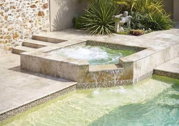 Diffazur - Le spa s'intègre parfaitement dans son environnement, en lien étroit avec la piscine. Sur son podium, il s'exprime avec du Crystalroc sable, de la pierre naturelle en margelle et un bandeau en émaux, sur 2 x 2 mètres, gagnant le Trophée d'Argent dans la catégorie « spa ». Réalisation Diffazur CPP.