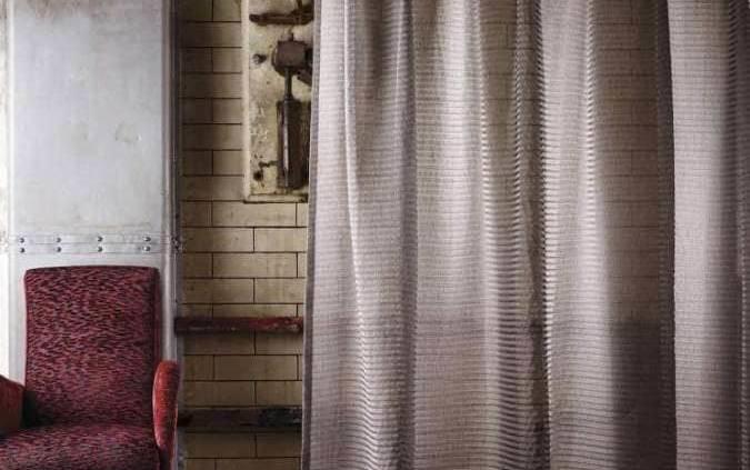 Le semi-voilage Positano irrite l'atmosphère, avec un mélange de lin, viscose et polyester. À ses côtés le fauteuil revêtu du tissu Guimard, un Jacquard velouté en viscose.