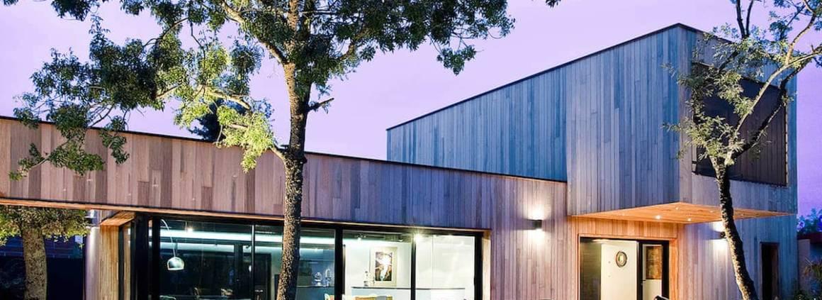 Cette réalisation met en exergue les menuiseries en aluminium Technal. La maison en ossature bois proche de Toulouse s'inscrit dans l'environnement. Son bardage bois en Red Cedar, joue sur les largeurs des lames, dans un esprit « cabane ». Généreusement ouverte sur l'extérieur, elle met en avant deux baies coulissantes Soleal, de plus de 7 mètres de longueur, associées à une menuiserie d'angle sur-mesure. À galandage, elles participent à la rythmique de la façade, à l'instar de la large baie fixe Geode de 3,63 mètres de hauteur. Elles permettent de profiter pleinement des apports calorifiques du soleil et d'accroître les perspectives de cette architecture réalisée par l'agence AR-QUO. Photographe Lucile Lossy. ©Technal