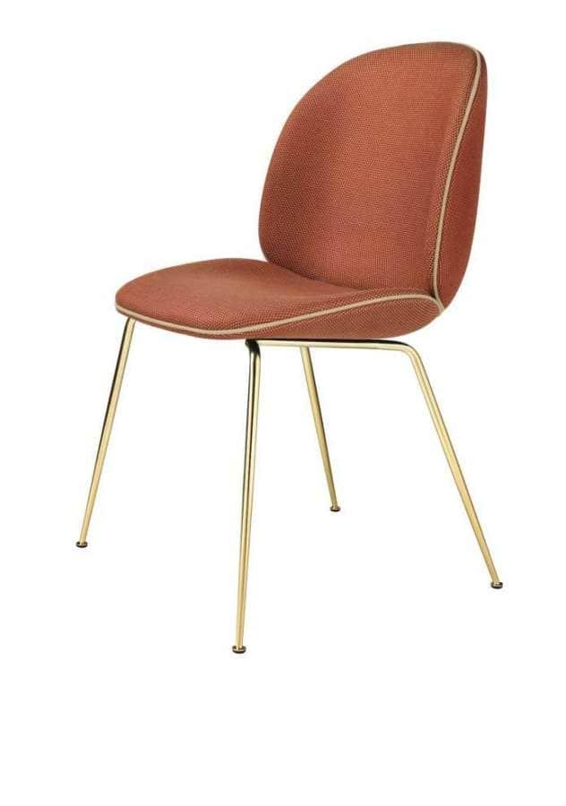 Gubi - Beetle Chair - L'iconique chaise imaginée par le studio GamFratesi en 2013 s'habille du tissu Backhausen Solo rouge et or. Le piétement est en laiton. ©Gubi