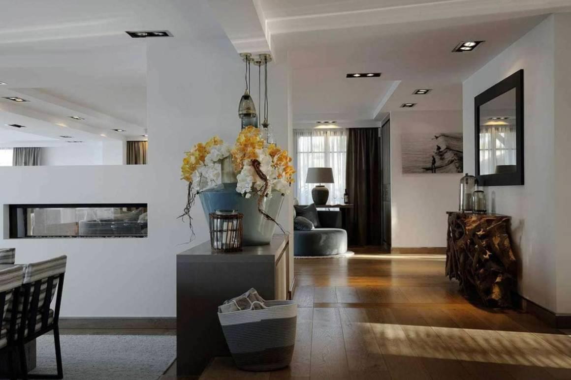 Transition entre le petit salon, la salle à manger, le salon panoramique, délimités par la cheminée au gaz. Réalisation Ikone® - Photographe Erick Saillet