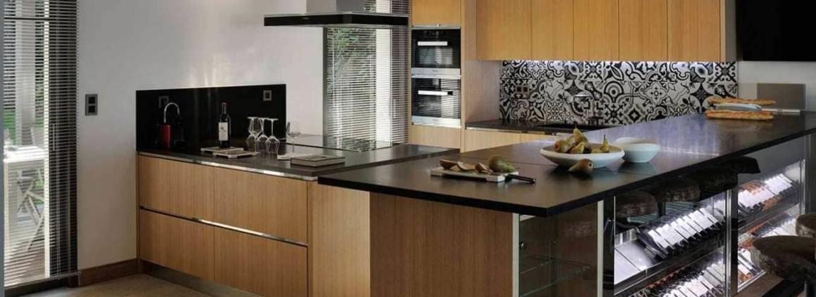 Espace cuisine réalisé sur-mesure en bois et inox, avec plan de travail en granit noir du Zimbabwe, carreaux ciment et cave à vin traversante. Réalisation Ikone® - Photographe Erick Saillet