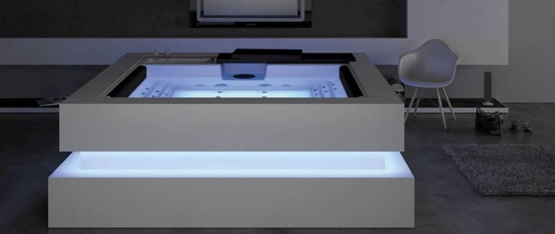 Spa cinq places Cube Ergo aux lignes contemporaines en Solid Surface ou disponible en graphite, chêne blanchi ou noyer. Il est équipé de 28 jets et de 14 buses d'air et de la technologie Colour Sense, avec 5 LED et accessoires éclairés. Traitement de l'eau par U.V. ©Aquavia