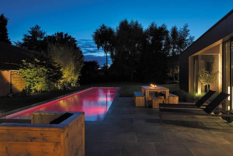 Couloir de nage de 16 x 3,51 pour une profondeur de 1,19 à 1,52 mètres, réalisé en blocs à bancher avec un escalier en angle. Revêtement intérieur liner coloris blanc illuminé par 4 projecteurs couleurs. Margelles et plages en pierres naturelles. ©Carré Bleu