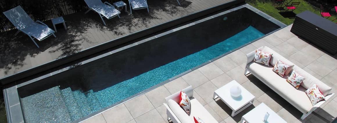 Couloir de nage de 9,70 x 2,10 mètres, en Gunite, avec une profondeur progressive de 1,20 à 1,70 mètres. Plage en carrelage et margelles en béton moulé plate grise. Le plus : la terrasse amovible, pour gagner en superficie. Récompensé par le prix d'Or, lors du 11ème Trophée de la Piscine et du Spa dans la catégorie «piscine citadine inférieure à 30 m2 de forme angulaire». Réalisation CPBR. ©Diffazur