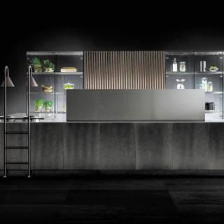 Le projet architectural D90/12 – D90/TP oscillant entre verre, acier, chêne et effet textile revisite le genre. Les matériaux animent la réflexion, jouant sur la transparence, la modularité mais également la mouvance. L'îlot évolue selon les besoins, avec un module télescopique pour distribuer les ustensiles et les épices dissimulés. Les contrastes se créent pour accentuer cette évolution, tant visuelle que structurelle. ©TM Italia