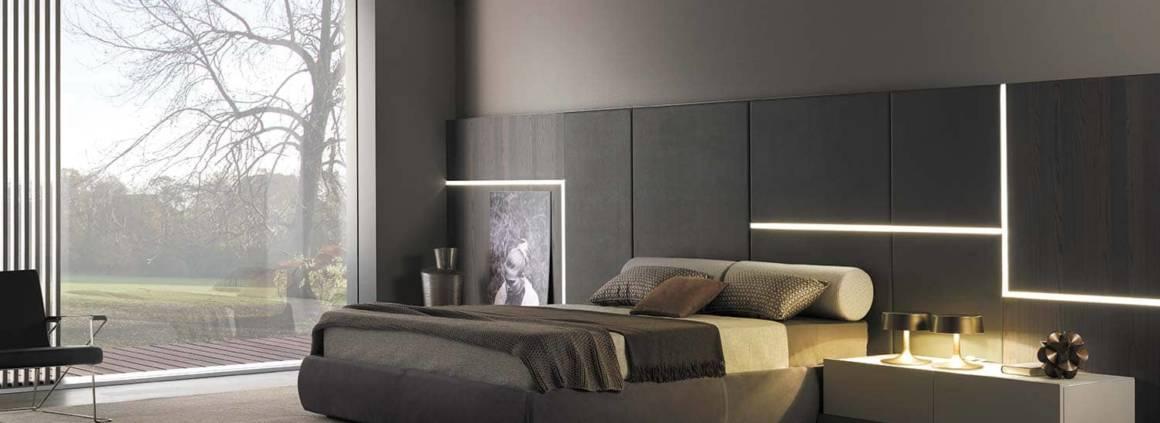 Composition onirique Ghiroletto avec cadre de lit recouvert d'un tissu amovible. Le système de boiserie intègre des solutions d'éclairage ou des ponctuations métalliques. Design Mauro Lipparini. ©MisuraEmme