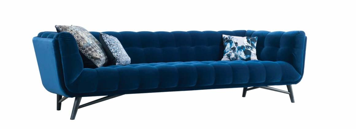 Canapé 4 places habillé de velours bleu Cabaret 100 % coton. Piètement en hêtre massif teinté wengé. Design Roberto Tapinassi & Maurizio Manzoni. L 279 x H 76 x P 95 cm. ©Roche Bobois