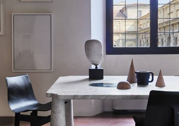 Agape Casa, Tre 3 et Eros - Rééditions des dessins de l'architecte Angelo Mangiarotti, qui s'illustrent par un jeu de construction par emboîtement. Table Eros en marbre de Carrare, associée aux chaises Tre 3 en bois et cuir. ©Agape Casa