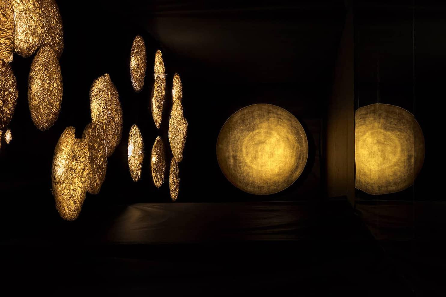 Milan Design Week 2017, Via Ventura dans le quartier de Lambrate - Enzo Catellani révèle sa scénographie de disques revêtus de feuilles d'or, éclairés par des micro-LEDs qui s'alternent en différentes hauteurs et dimensions. Il rend hommage au soleil et à son dialogue permanent avec la chaleur et l'ombre. Soit le luminaire par l'éveil des sens - ©Catellani&Smith