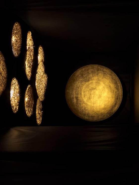 Milan Design Week 2017, Via Ventura dans le quartier de Lambrate. Enzo Catellani révèle sa scénographie de disques revêtus de feuilles d'or, éclairés par des micro-LEDs qui s'alternent en différentes hauteurs et dimensions. Il rend hommage au soleil et à son dialogue permanent avec la chaleur et l'ombre. Soit le luminaire par l'éveil des sens. ©Catellani&Smith
