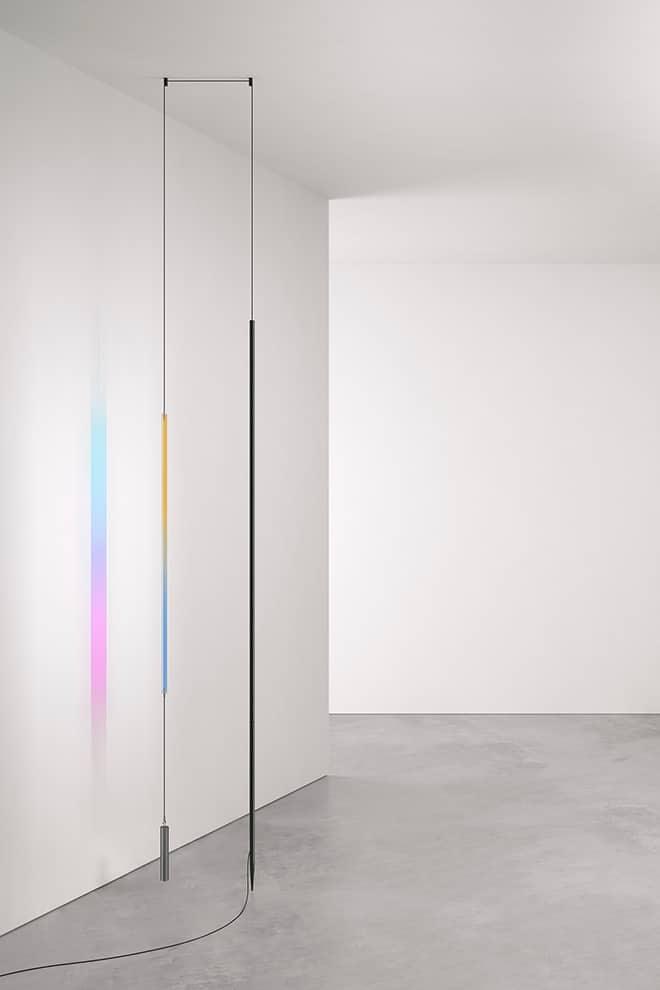Composition Blush Lamp équipée d'un bandeau LED et d'un verre dichroïque qui projettent des reflets colorés - Disponible en 3 finitions aluminium, blanc ou noir - Design Formafantasma. ©Flos