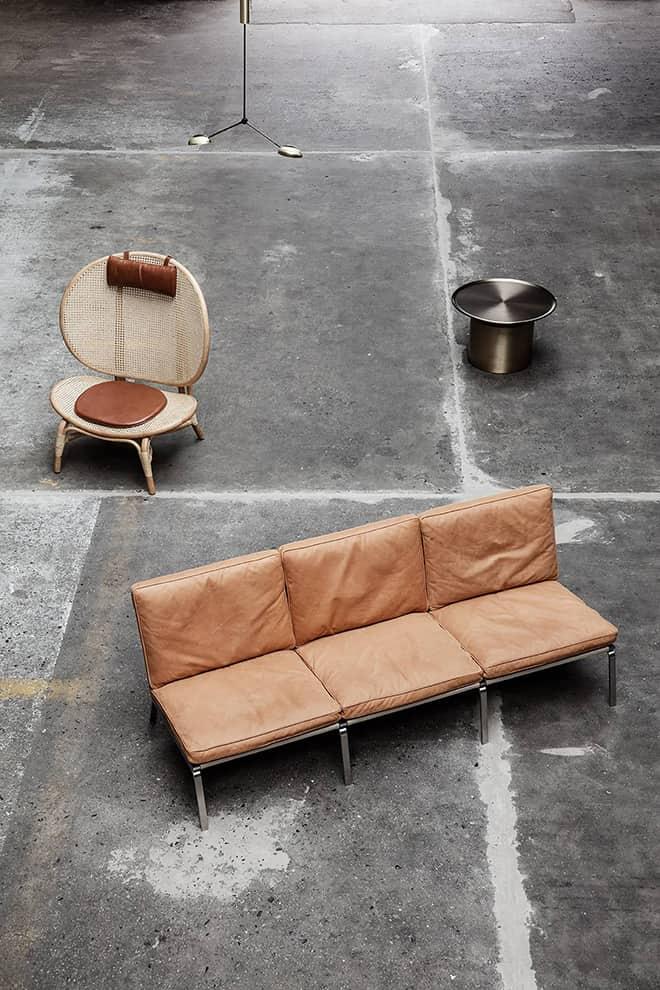 NORR11 - Fauteuil Nomad Man en bambou et cuir. L 90 x P 77 x H 100 cm. Sofa 3 places en acier et cuir vintage. L 197 x P 74 x H 75 cm. ©NORR11