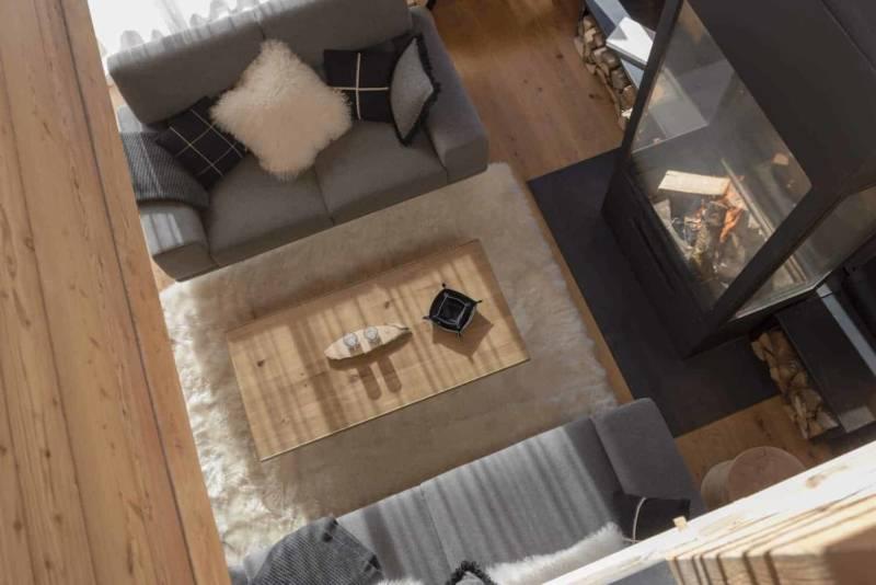 Vue sur le salon depuis le dernier étage. Canapés en laine Arpin, réalisés sur-mesure par L'Atelier des Frères. Table basse Newton version Small de Riva 1920. Cheminée télescopique sur-mesure créée par Piros.
