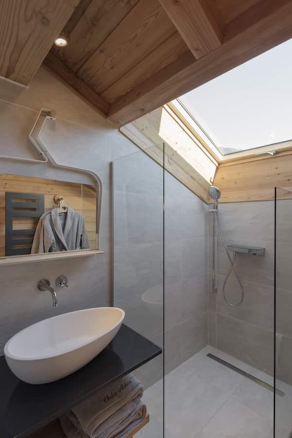 La salle de bains avec robinetterie douche Select de Hansgrohe chez Richardson. Au mur, miroir Rencontre créé par Benoît Chabert, Altiligne, qui reflète le peignoir Sensei La Maison du Coton et les cintres Pure « R », personnalisés par Alphanger, avec liserés de tissus Arpin sur les épaules, reprenant le code couleur propre à chaque chambre.