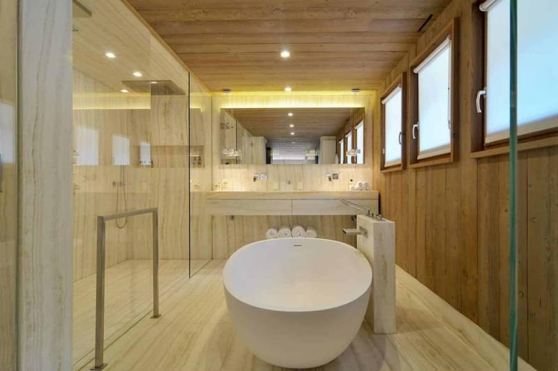 La salle de bains mixe une cabine de douche en verre fumé et la baignoire îlot Drop, d'Agape. Ici, la pierre d'Antolini est plus discrète, laissant le bois prédominer. Robinetterie bain Supernova et vasque Tara Logic de Dornbracht.