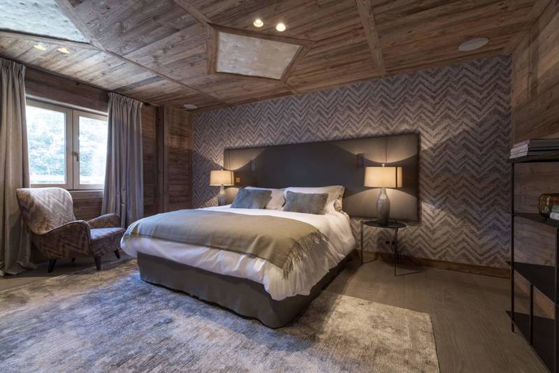 Chalet Luxor Megève - À chaque chambre, son ambiance. Dans une chromatique plus sombre, cet espace nuit s'habille de cuir sur la tête de lit et revêt au mur un motif chevron Cadance d'Arte International repris sur le fauteuil. Luminaires en verre soufflé et tissu Guaxs.