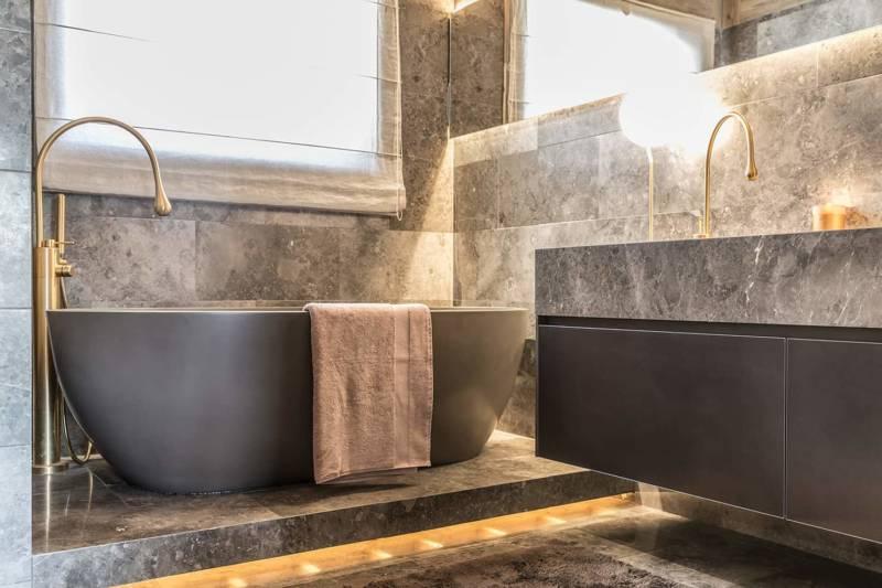 Chalet Luxor Megève -La salle de bains de la master suite se teinte de la Pierre Gris du Marais brunie par la chaleur des luminaires et le laiton de la robinetterie Goccia, de Gessi. Meuble Modulnova et baignoire Cielo.