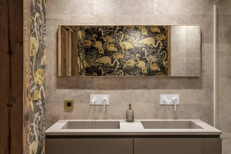 Chalet Luxor Megève -Toujours accompagnée d'une salle de bains généreuse, qui met en avant, ici, le revêtement mural Flamingo d'Arte International. Robinetterie Treemme. Appareillage CJC.