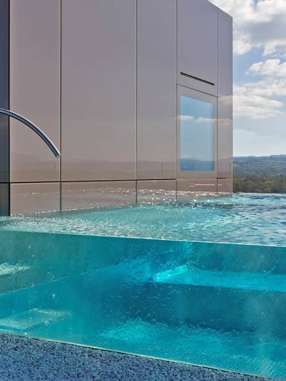 Piscine installée en Suisse, sur un toit-terrasse. Trophée d'argent 2017 dans la catégorie «Piscine installée à l'étranger». Bassin en verre et inox de 7 x 3 mètres avec une profondeur de 0,95 à 1,43 mètre. Escalier intérieur et extérieur en verre méthacrylate. ©Carré Bleu