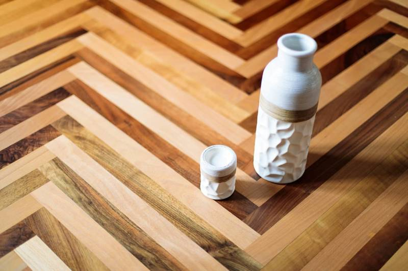 Ici, le mélange du noyer et du hêtre crée un mariage insolite rehaussé par l'assemblage en bâtons rompus. Disponible en parquet massif ou contrecollé, réalisable sur-mesure. ©Émois & Bois