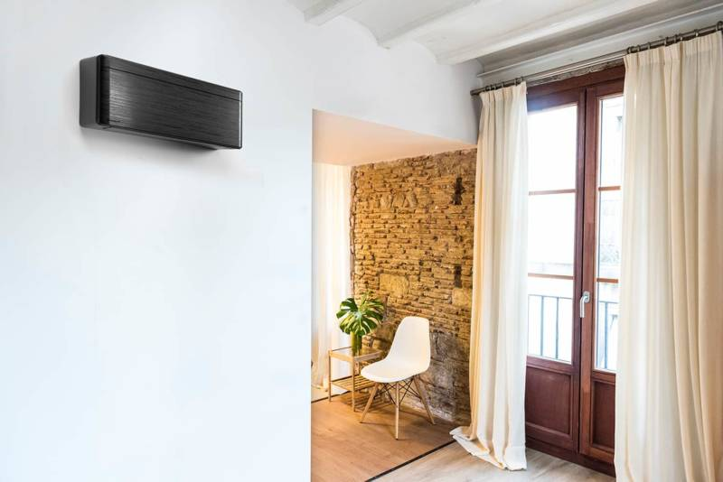 Gamme murale de climatisation réversible, Stylish Bluevolution, caractérisée par la finesse de ses lignes et son design compact (H 29,5 x L 79,8 x P 18,9 cm). Pilotage à distance via la technologie WiFi intégrée. Niveau sonore le plus faible du marché : 19 dB(A). 3 finitions possibles, dont noir, imitation bois. Classée A+++. ©Daikin