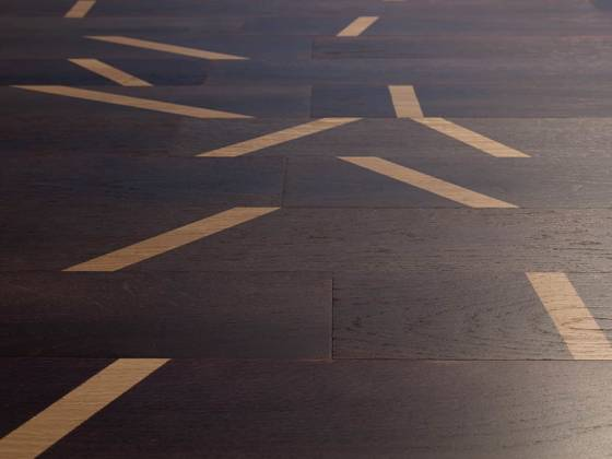 Le parquet contrecollé Scotch, en rouvre, s'illustre par une empreinte graphique et artisanale, avec une empreinte de scotch aléatoire, devenant un signe distinctif. Lame 800/1300 x 110/120 mm. Chanfreinée sur les 2 ou les 4 côtés. ColorSuite. En vernis brillant, mat ou bio. Compatible chauffage au sol. Design Gio Tirotto. ©Menotti Specchia