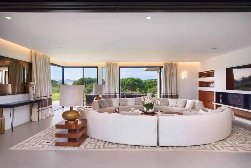 Le salon réception adoucit la linéarité omniprésente, avec sa pièce centrale : les canapés circulaires Nelson de PH Collection.