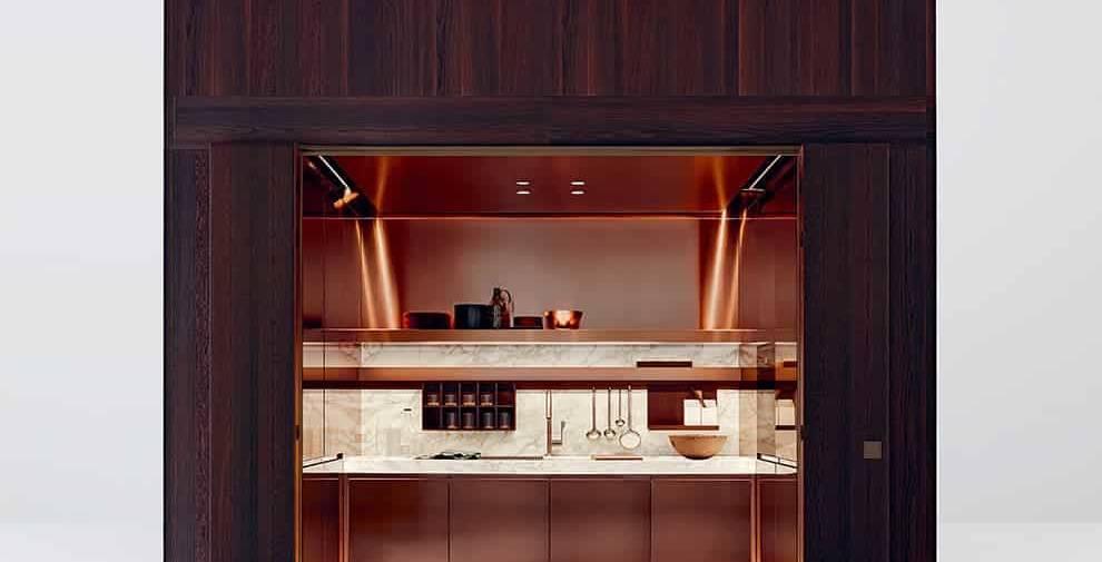 Partie charme du nouveau concept contemporain d'Arclinea, cette boîte se définit par une architecture enveloppée de boiserie, un chêne fumé NTF, allié au nouveau système Modus de portes pliantes horizontales à 180°. Les portes de 4 cm d'épaisseur sont disponibles en 40,6 et 50,6 cm de largeur par 234 et 252 cm de hauteur. Le cube sur-mesure renferme un espace de travail complet, avec plan de travail et éclairage ambiant. ©Arclinea