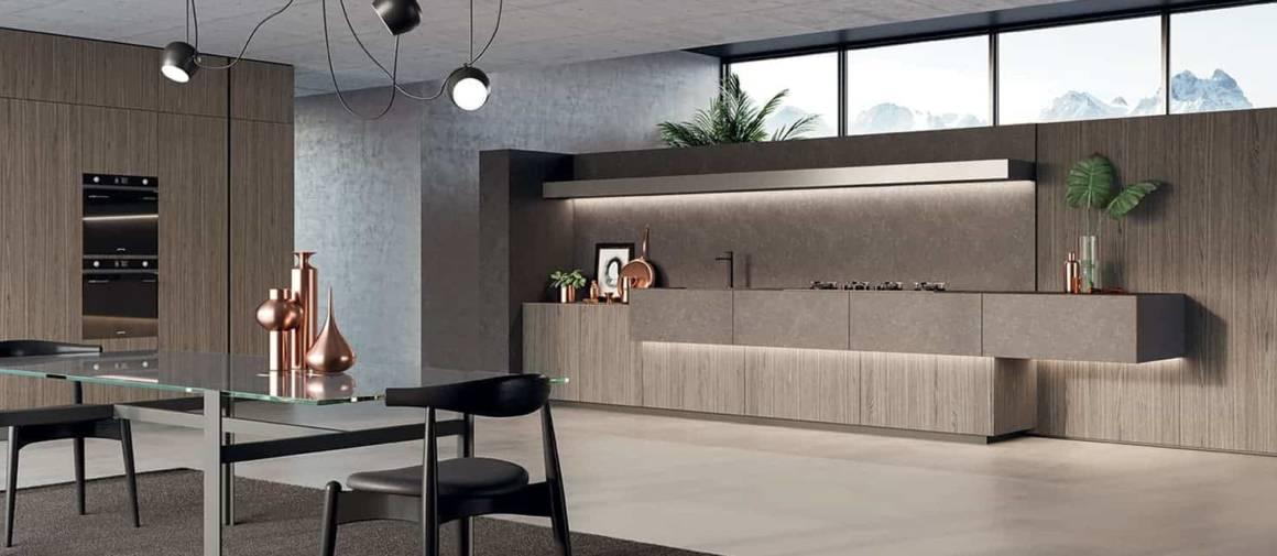 La cuisine Monolith Wall fait la part belle à l'espace central sans se départir de rangements généreux. La structure en pierre claire Estatuario repose sur des meubles bas laqués ferro calamina, créant un ensemble contrastant. Plus loin, la paroi Eucalypto grigio développe l'espace culinaire dans l'angle, en dissimulant les colonnes à portes encastrées. ©Comprex