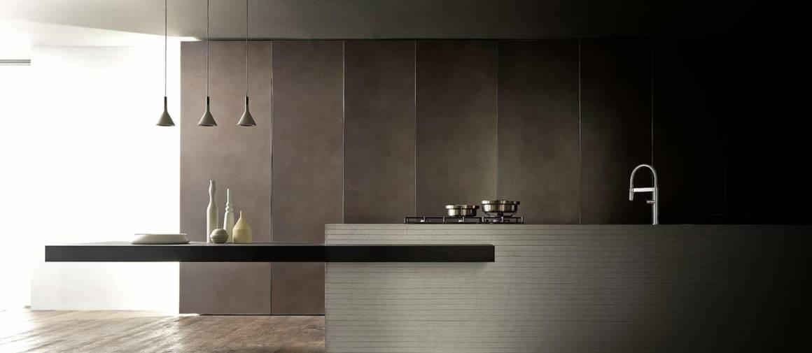 Complètement intégrée dans l'espace domestique, la Twenty Royal Grey fusionne avec l'architecture d'intérieur et ses volumes, balayant le concept de meubles de cuisine au profit d'un agencement. L'îlot en marbre avec un plan de travail en Royal Grey s'inscrit dans cette démarche avec une construction en strates, jouant sur le clair-obscur, associée à une table en bois d'eucalyptus. Portes terre-plafond en alvéolaire d'aluminium avec finition Bronze Dust. Design Andrea Bassanello. ©Modulnova.