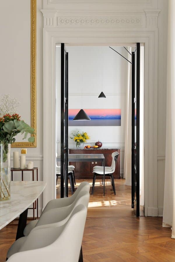 Traversante, la salle de réception jette un œil à l'est sur la cuisine et à l'ouest la master suite, l'ensemble de la circulation ponctuée par des portes pivotantes en acier laquée noire.