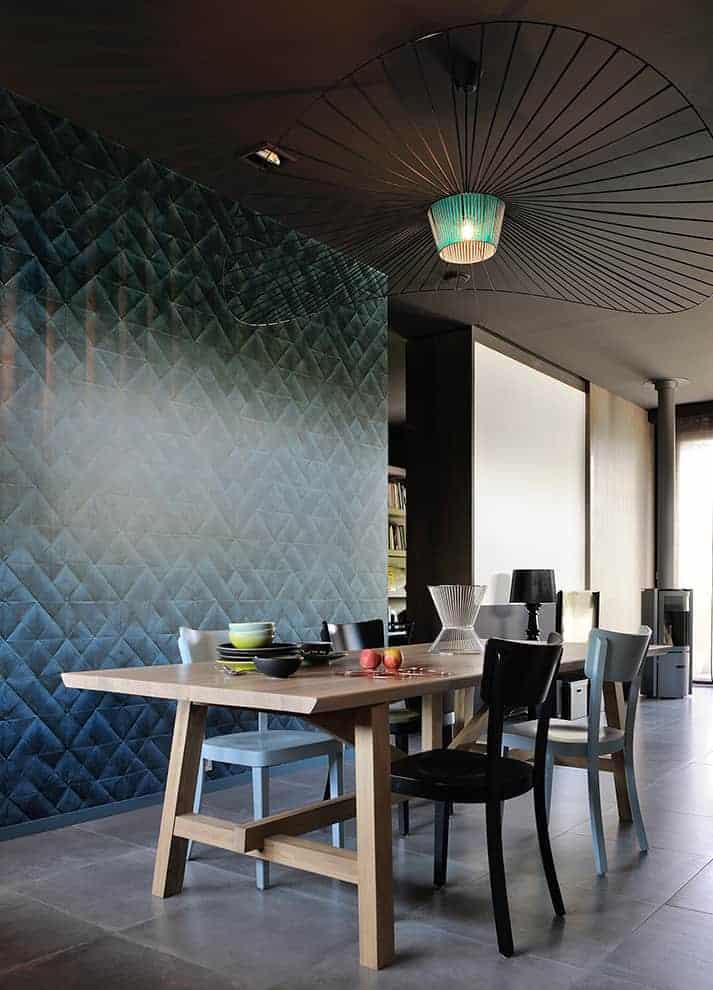Dès l'entrée, la salle à manger, lien entre le salon et la cuisine, donne le ton. Chaises Bistrot, table en bois massif, luminaire Vertigo, Petite Friture. Au mur, le papier peint Pleats, Elitis.