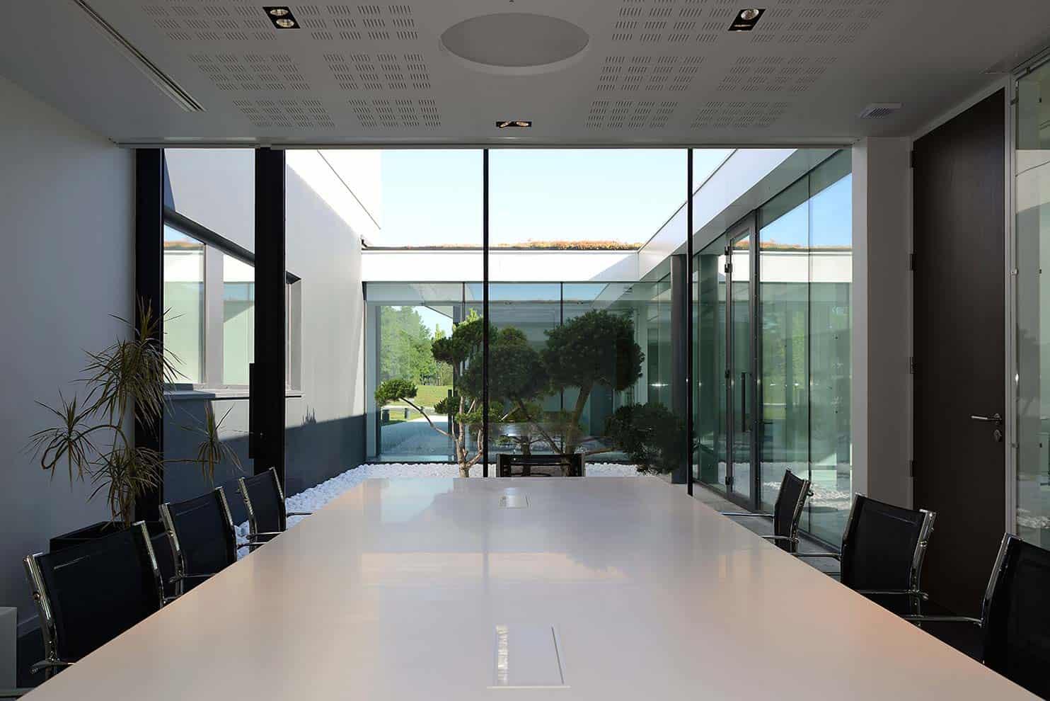 Salle de réunion en lien avec le patio, via les vitrages minimalistes, sans cadres, réalisés sur-mesure. Architecte Pierre Minassian - Agence au*m Photographe Erick Saillet