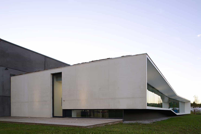 Bloc en béton gris accueillant les bureaux. Bloc en béton noir accueillant l'entrepôt. Architecte Pierre Minassian. Photographe Erick Saillet