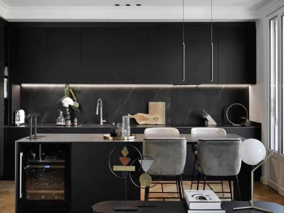 Réalisée sur-mesure par l'artisan-ébéniste, la cuisine multiplie les rangements dissimulés par les façades en FenixNTM, tandis que la crédence et le plan de travail revêtent la céramique Storm, d'Inalco. Elle s'anime grâce à la conception lumière, flattant les matériaux avec le ruban sous les modules en hauteur ou valorisant l'îlot avec le système innovant Move It de chez Xal, un rail magnétique. Lampes de table Rever Dining 1.0, Wever & Ducré. Au plafond, moulures de chez Orac Décor.