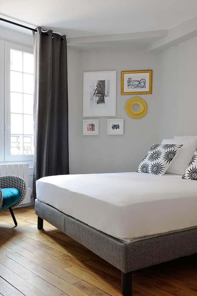 La chambre, avec son parquet d'origine, se distingue avec des teintes plus douces et un style plus sobre.